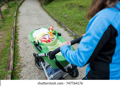 Mother pushing baby in a stroller.