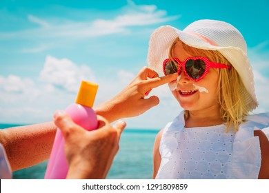 mother put sunblock cream on little daughter face at beach