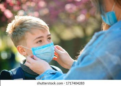 Mother puts her son a face protective mask outdoors. Coronavirus, illness, infection, quarantine, medical mask, COVID-19. Coronavirus quarantine. Closeup medical mask. Kid wearing face mask.