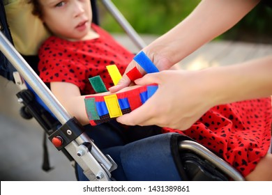 Mother puts on her daughter arms orthosis. Disabled girl sitting on a wheelchair. Child cerebral palsy. Means of rehabilitation. Inclusion.