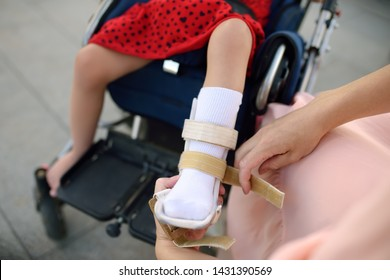 Mother puts on her daughter legs orthosis. Disabled girl sitting on a wheelchair. Child cerebral palsy. Means of rehabilitation. Inclusion.