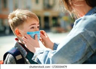 Mutter legt ihrem Sohn eine Sicherheitsmaske auf das Gesicht. Der Schuljunge ist bereit, zur Schule zu gehen. Junge mit Rucksack im Freien. Zurück zum Schulkonzept. Medizinische Maske zur Vorbeugung gegen Coronavirus. Coronavirus-Quarantäne