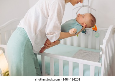 Mother puts sleeping baby in to the crib
