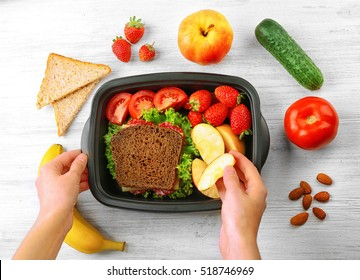 Mother putting food in lunch box, top view