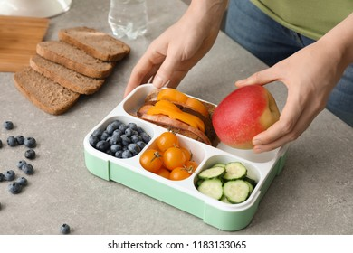 Mother putting food for schoolchild in lunch box at table, closeup