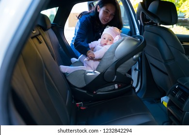 Mother putting her baby in baby chair on the backseat of the car, viewed from the other side of the vehicle