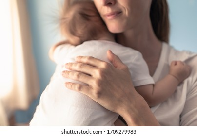 Mother putting her baby to sleep. Parenting and nap time concept.