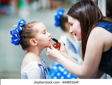 Mother putting lipstick on her daughter on mirror background. Woman helping little gir to use lipstick before a dance performance. Mom makes make-up her daughter. Selective focus.