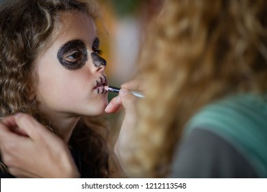 Mother putting makeup on little goth girl face. Child in background, focus on little girl.. Skull face paint, dark black eyes. Blond, curly hair, beautiful kid. Depth of field. Woman turned with back.