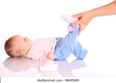 Mother putting shoes on baby leg