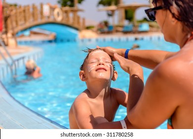 Mother putting sunscreen on her sons face as he sits alongside a swimming pool with his face tilted back to the sun