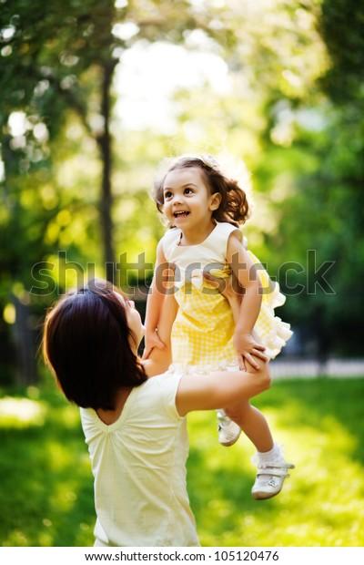 Mother raising her little daughter up high