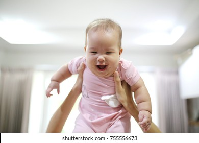 mother reach hand lift up play and show throws cute happy baby on sky in house living room at morning time after awake concept. enjoy parenting emotion and good feeling family.