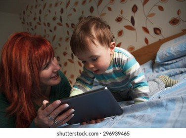 Mother reading bedtime stories to her son on digital tablet