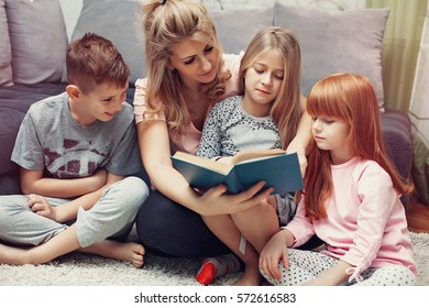 Mother reading a book to her children