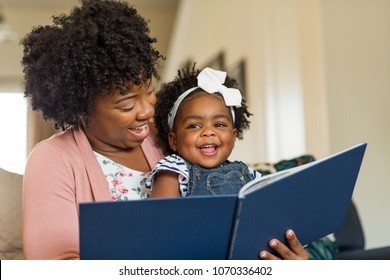Mother reading a book to her daughter.