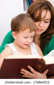 Mother is reading book with her son, indoor shoot