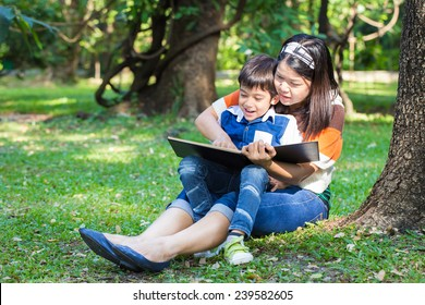 Mother reading a book with her son in park under the tree