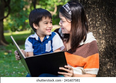 Mother reading a book with her son with smile face in park under the tree