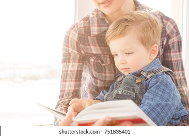 Mother reading book for her son. Mother and son sitting embracing and reading book together.