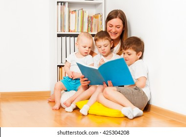 Mother reading book to her three age-diverse kids