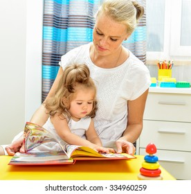 Mother reading a book to little baby. Indoors.
