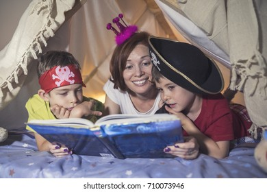 Mother reading a fairy tale to her sons at bedtime