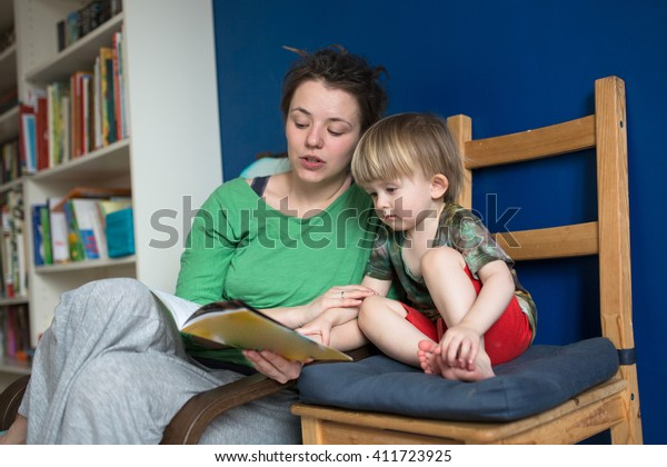 Mother reading with her son at home, casual, real interior, blue wall, lifestyle