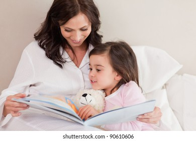 Mother reading a story to her daughter in a bedroom