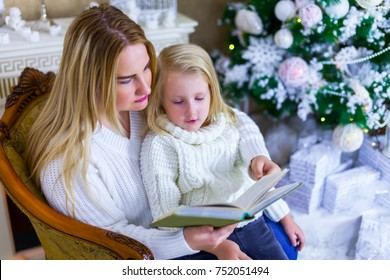 Mother reads a book to her daughter in a Christmas interior