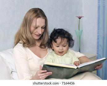 Mother reads to the child the book.