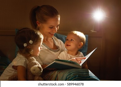 mother reads to children the book before going to sleep in bed