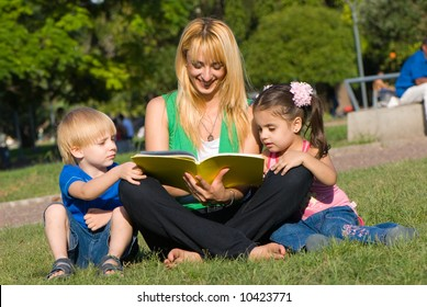 Mother reads to children of the book on a glade in park