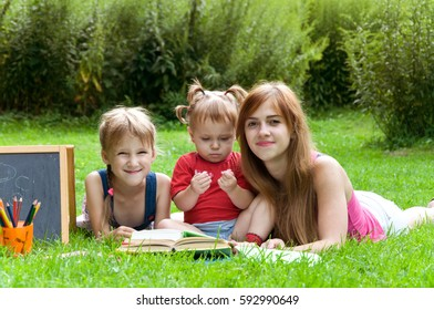 mother reads to her children an interesting book in the park
