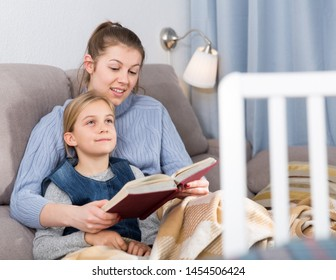 Mother reads an interesting book for her daughter