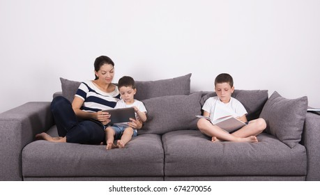 Mother reads an interesting book with her sons of the sofa. Studio portrait on white background.