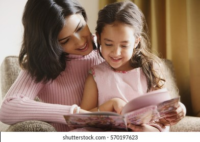 mother reads story book to her daughter