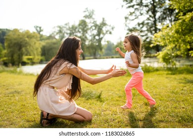 Mother ready to hold daughter running towards her