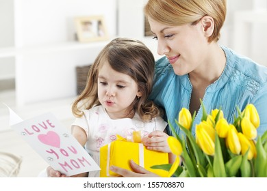 Mother receiving bunch of flowers from her daughter