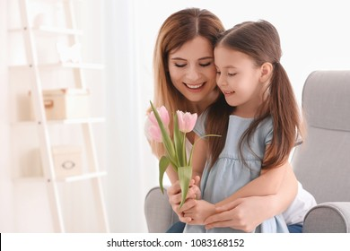 Mother receiving flowers from her cute little daughter at home