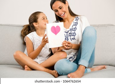 Mother receiving a greeting card on mother's day from her daughter