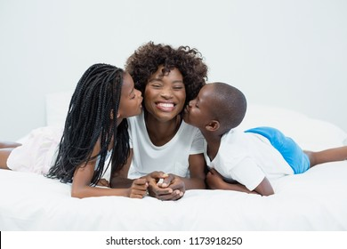 Mother receiving kiss from their kids in bedroom at home