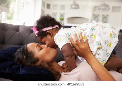 Mother reclining, holding and kissing her toddler daughter
