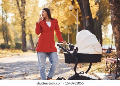 Mother in red coat have a walk with her kid in the pram in the park at autumn time and smoking.