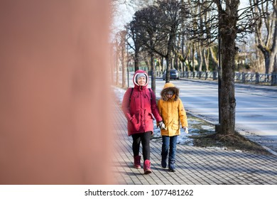 Mother in red jacket and young daughter in yellow walking on the urban street, view from the corner