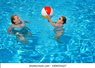 Mother relaxing in swimming pool with her daughter