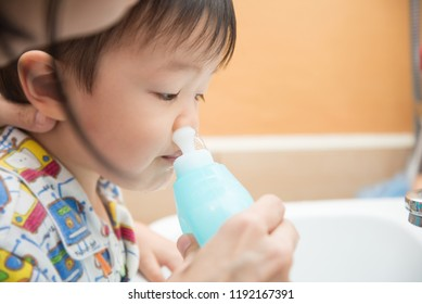 Mother rinse baby boy nose with salt water to cleanse the nose