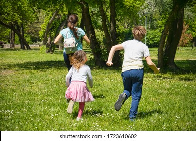 Mother running with her 9 year old son adn 4 year old daughter outdoors on green grass in spring time.