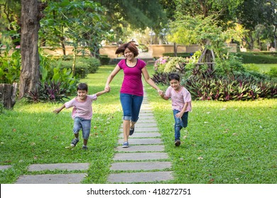 mother running in the park with sons
