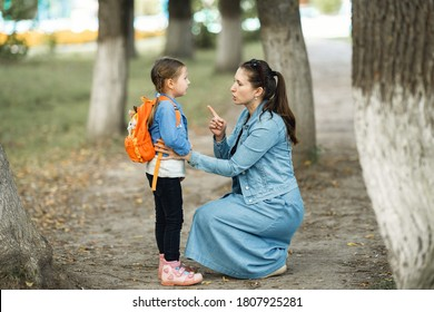 mother scolds her daughter in the street. A child cries, a woman shakes her finger because of the girl's bad behavior, while walking in the Park. Education. Rule of conduct.
